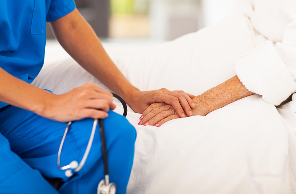 Photo of a nurse holding the hand of an elderly patient