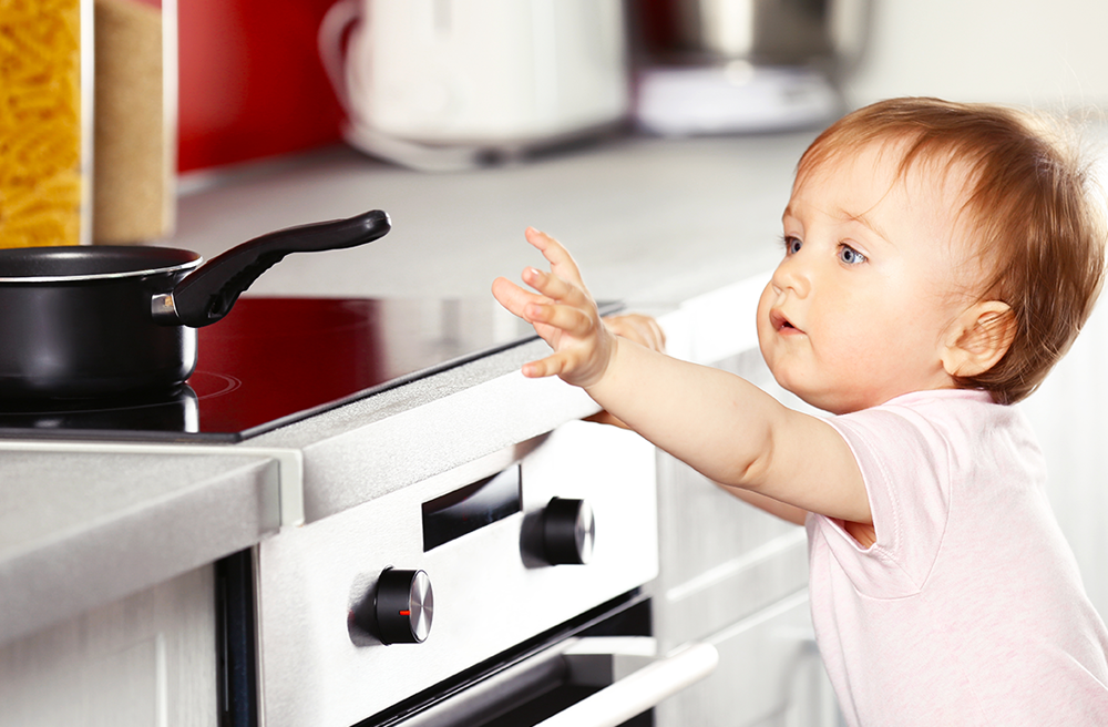 Photo of a toddler reaching up at a pot on a stove