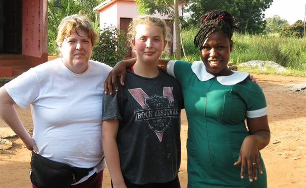 Photo of Donna Alden-Bugden and daugther Olivia with public health nurse Vivian Dordoe at a clinic in the Volta region of Ghana
