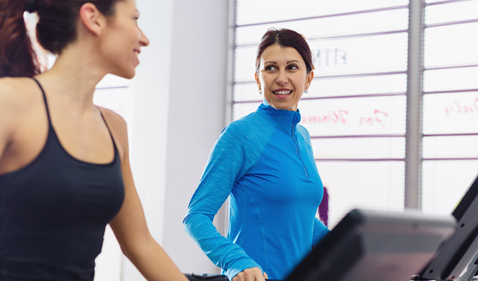 Photo of two women on treadmills at the gym