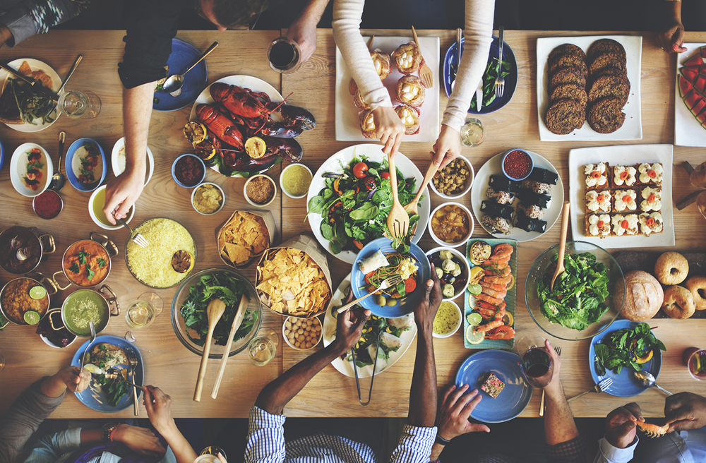 Bird's eye photo of people sitting a large table full of food