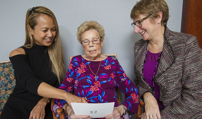 Photo of Misericordia Place resident Bruna Dandri looking over an eye test card with vision screening team members Mary Ann Masesar and Karen McCormac