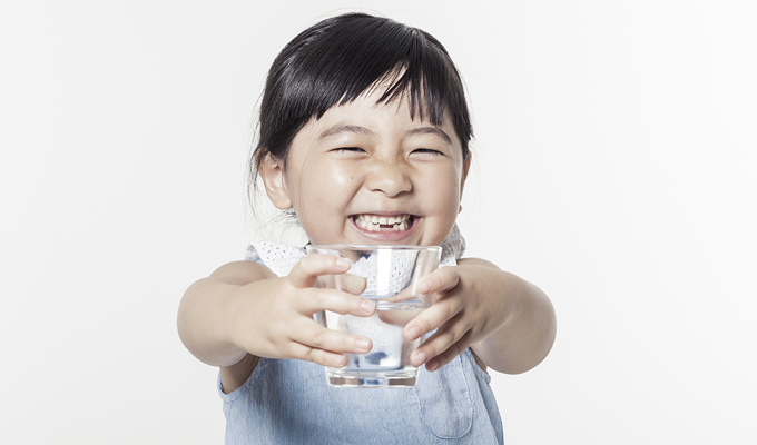 Photo of a young girl holding a glass of water