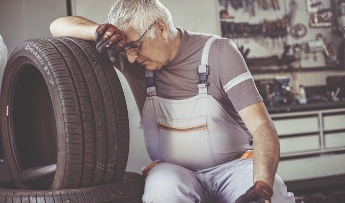 Photo of a tired man leaning on a tire